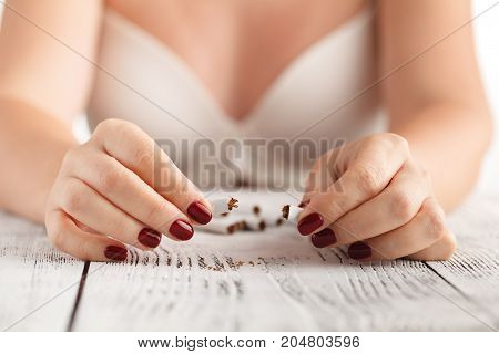 Woman hands breaks down the cigarette on table