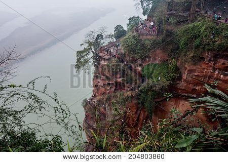 Climbing the stairs in the Buddha mountain overlooking the water. View from the top of the water and the huge rocks of Buddha. Buddha-giant Leshan is a stone statue 71 meters high (233 feet) high. We rise on a mountain.