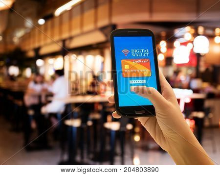 Ecommerce smart pay business and technology concept.A digital wallet to pay for goods and services to convenient and fast with blur restaurant background.