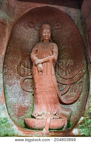 The Buddha statue in Leshan, China. The image of a woman in a rock in full growth