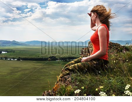 The girl sits on the mountain and looks into the distance. At the bottom are green fields.