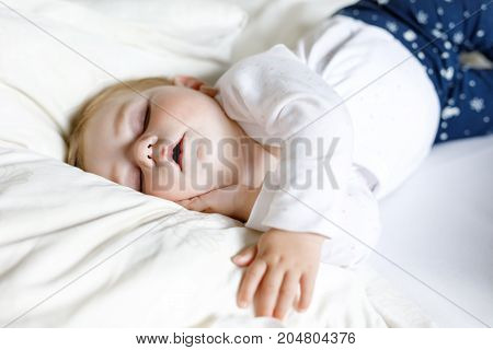 Cute adorable baby girl of 6 months sleeping peaceful in bed at home. Closeup of beautiful child, little newborn kid sleeping.