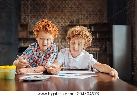 Two peas in a pod. Joyful concentrated kids sitting next to each other and focusing their attention on pieces of paper while getting creative and painting something interesting together.