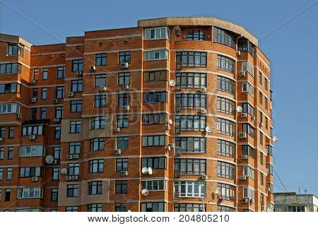 Brown multi-storey house with windows and balconies on the sky