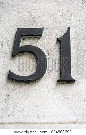 Number fifty one in dark figures on white wall