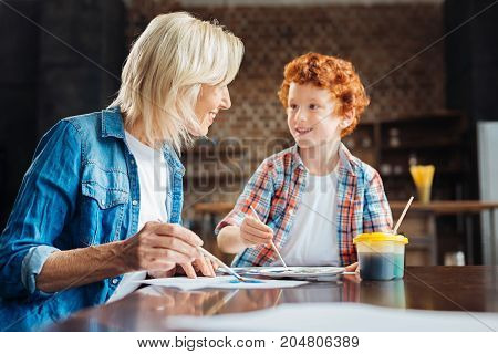 Do you know. Selective focus on a positive minded elderly lady smiling while looking at her cute redhead son telling her something while both working on their masterpieces at home.