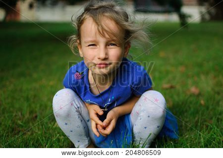 The baby is squatting and looking at the camera. The girl's eyes narrowed ironically. She holds a purple clover flower in her mouth
