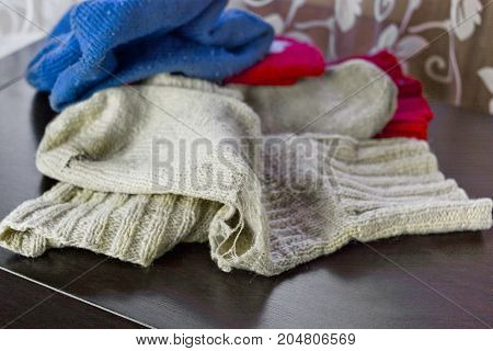 Rugged woolen socks and other warm clothes laid on a table top in mess