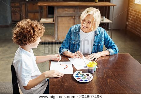 How was your day. Selective focus on a beautiful elderly woman looking at her curly haired grandchild while asking him about something during a family painting session