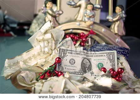 One dollar bill in focus and Christmas gifts in the blurred background. Selective focus studio shot