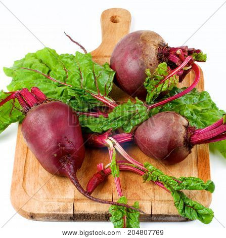 Arrangement of Fresh Raw Organic Beet Roots Full Body and Young Sprouts with Green Beet Tops on Wooden Cutting Board on White background
