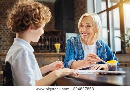 Grandchildren are the blessing from above. Selective focus on a beaming senior woman grinning broadly while looking at her curly haired grandson painting with her while spending time at home.