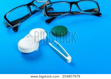 glasses contact lenses in containers and tweezers on blue background.