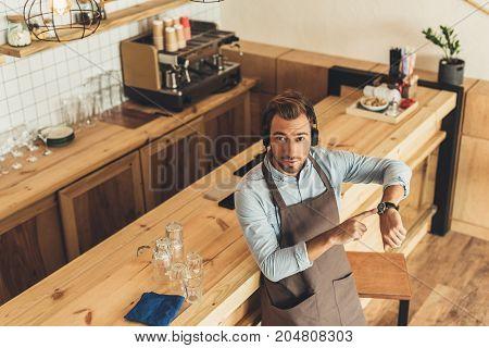 Barista In Headphones In Cafe