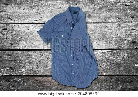 Casual shirt on the wooden background. Top view