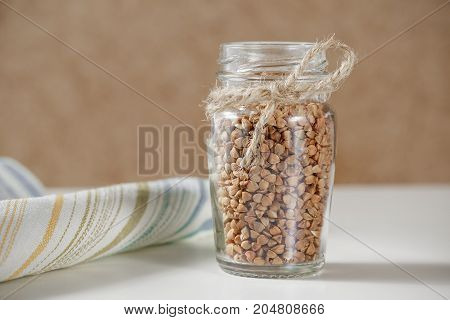 Uncooked Buckwheat In Glass Jar Close Up