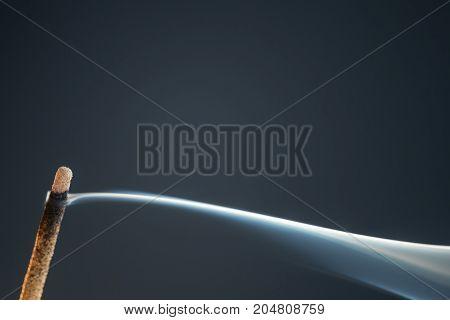 Smoking drifting from a lit joss stick on a black background.
