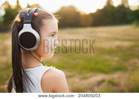 cute child having nice rest outdoor, beautiful girl with black and silver headphones listening music on nature