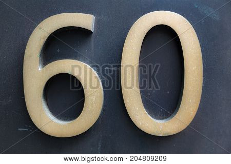 Elegant number sixty in soft gold on dark background