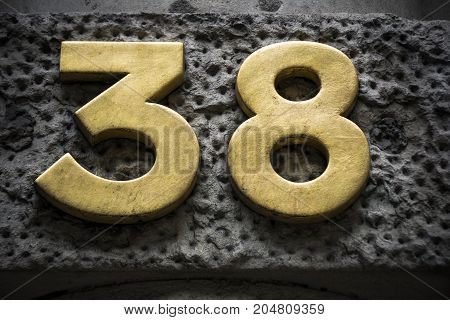 Golden number thirty eight on dark wall
