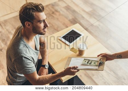 Man Paying For Order In Cafe