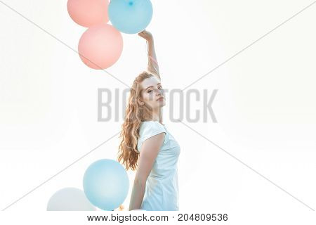 portrait of young beautiful woman with flying multicolored balloons against the sky.  soft light