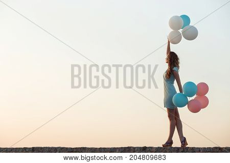 young beautiful woman with flying multicolored balloons against the sky. happiness and dreams concept