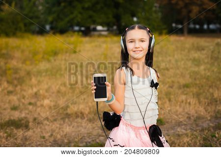 cute girl showing her phone on nature, cute little girl holding her phone and listenng music in white blouse and pink fluffy skirt