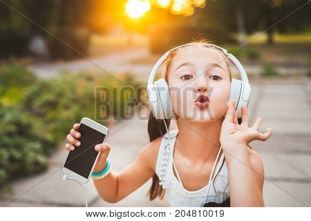 girl with headphones sending air kiss to somebody, cute and pretty child making sweet gesture