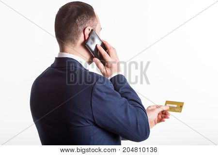 businessman in a blue suit dictates by phone the data from a credit card. Back view