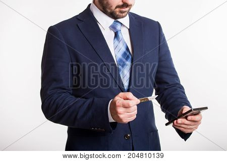 businessman in blue suit enters credit card information into black phone