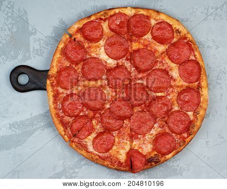 Freshly Baked Pepperoni Pizza with Tomato Sauce Pepperoni and Cheese on Cutting Board on Grey Textured background. Top View