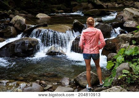 a woman is standing next to a big river rapids in the forest