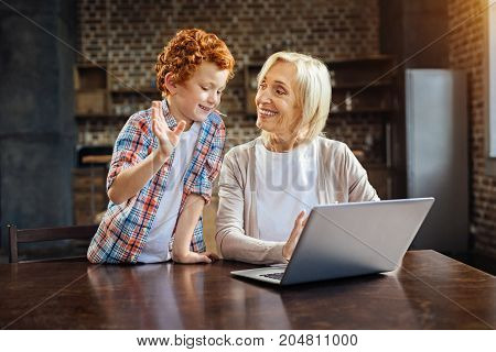 Heartwarming stories. Emotional redhead boy gesturing while having a pleasant conversation with his smiling grandma working on laptop at home.