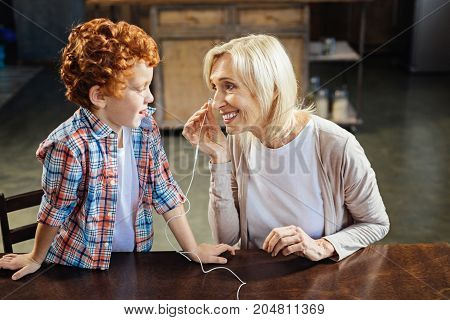 Love and understanding. Selective focus on a smiling elderly lady sitting next to her adorable grandchild while putting earphones on and preparing for listening to music together.