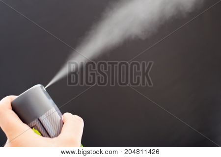 Aerosol can held in hand with black background
