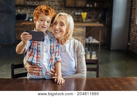 Say cheese. Loving grandmother embracing her curly haired grandson standing on a chair while both smiling into the camera of a smartphone and taking a self portrait together.
