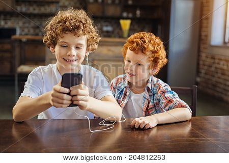 Turn on this one. Adorable shot of two different aged kids sitting next to each other and focusing their attention on a screen of a smartphone while both listening to music at home.