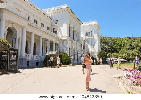 Yalta, Crimea - 11 July, People in the square near the palace, 11 July, 2017. Architecture of the Levada Palace in Yalta.