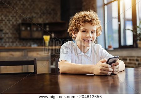 Love this song. Portrait of a curly haired boy looking into the camera with a cheerful smile on his face while relaxing and listening to his favorite music.