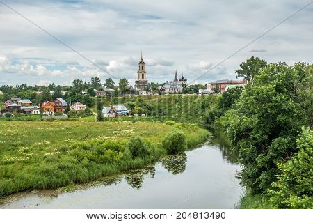 Image of picturesque pesage, wooden houses, church, river on summer day