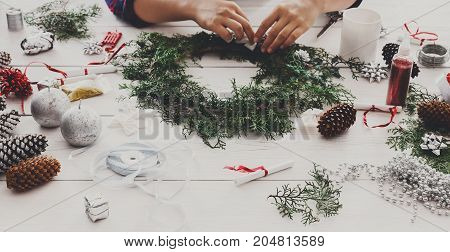 Christmas handmade diy background. Making craft xmas wreath and ornaments. Woman's leisure, tools and trinkets for holiday decorations on white wooden table with female hands.