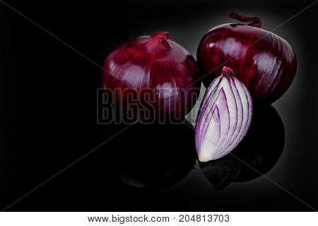 Red Onion And Half Slice On Black Background With Reflect.