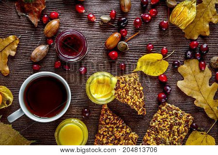 Autumn still life with hot tea, honey and berries on wooden background.