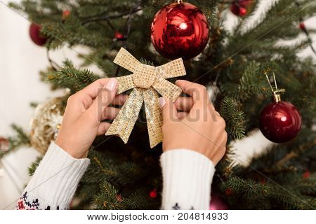 close-up partial view of woman decorating christmas tree