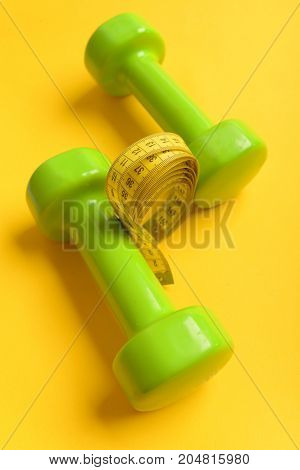 Athletics And Weight Loss Concept. Dumbbells In Bright Green Color
