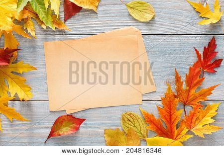 Autumn colorful maple leaves framing craft paper sheet for copy space on rustic wood background. Seasonal fall sales mockup, top view