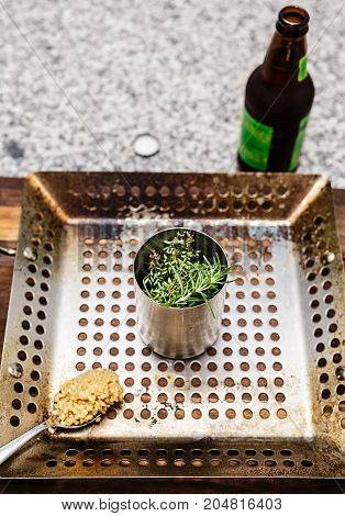 A beer can chicken grilling pan with rosemary and thyme in the cup. A bottle of beer and a spoon of minced garlic also shown.