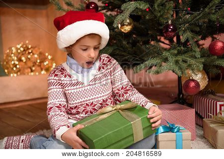 cute surprised little girl in santa hat holding christmas present at home