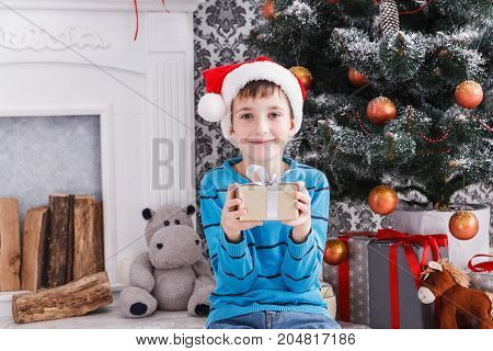 Cute happy boy in santa hat with christmas present box on holiday morning in beautiful room interior. Male child open Xmas gifts near big decorated fir tree and fireplace. Winter holidays concept